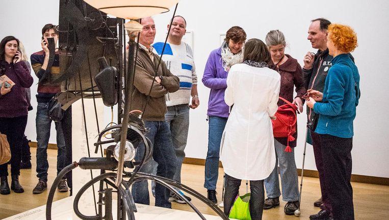 Melanie Ciuraj (midden, in het wit) van Oogtours leidt een groep door de Tinguely-tentoonstelling in het Stedelijk Beeld Dingena Mol