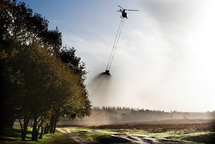 Een helikopter strooit kalk boven de Ginkelse Heide.