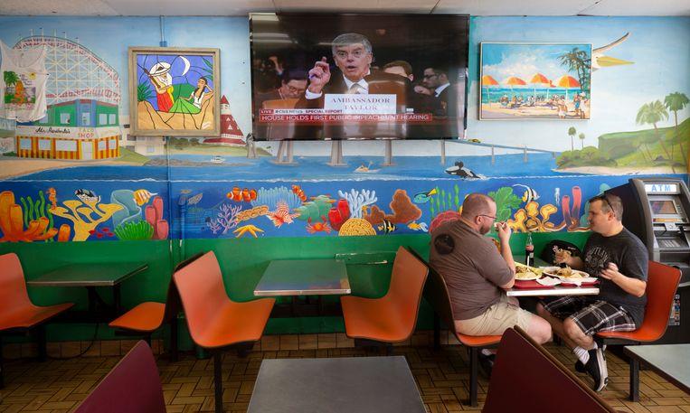 De televisie met de openbare impeachment-hoorzittingen staat aan in een Mexicaans restaurant in San Diego.  Beeld AP