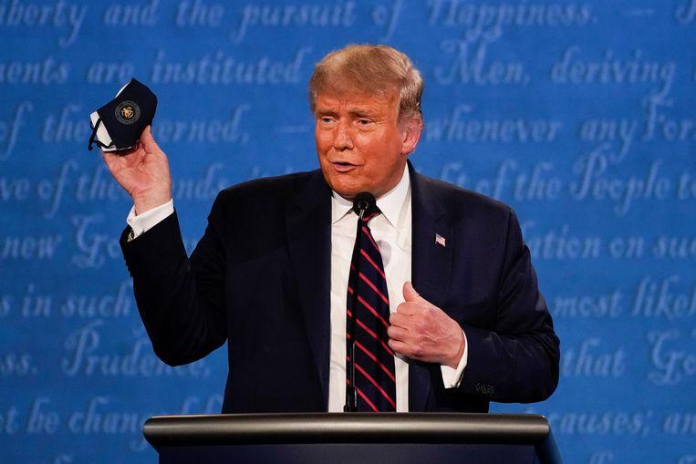 Trump houdt een mondkapje omhoog tijdens het debat met Biden eerder deze week in Ohio. Beeld AP