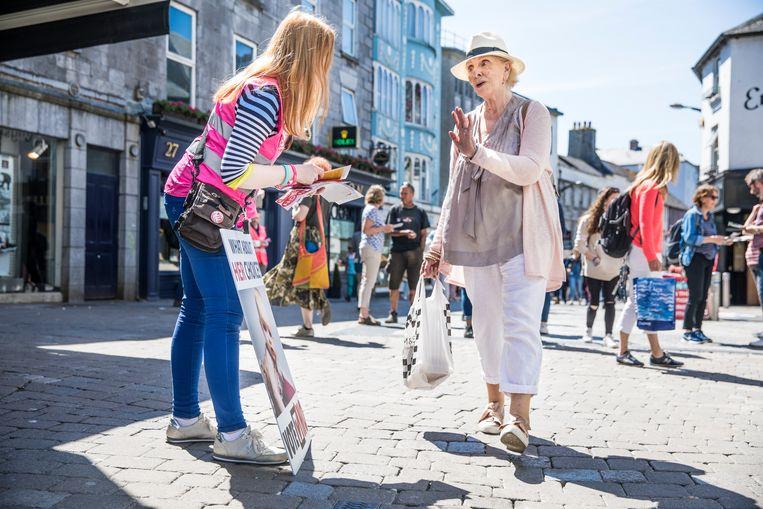 Een anti-abortusactivist deelt folders uit in een winkelstraat in Galway.  Beeld Marlena Waldthausen