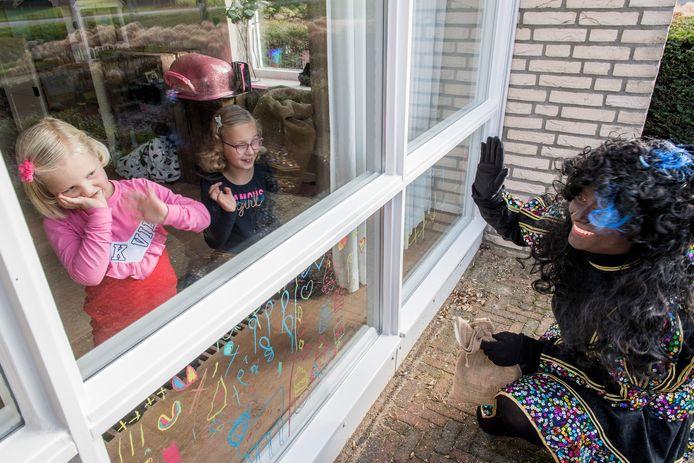 Vanwege corona zijn de Sinterklaasintochten afgelast dus komen de pieten in Beesd langs de huizen van kinderen om een klein presentje te brengen,  zoals hier bij Iefke de Wit (linksr) en haar zusje Yinthe.