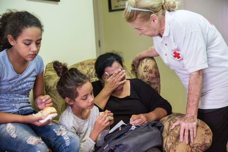 Een grootmoeder en haar twee kleinkinderen krijgen op Aruba wat te eten bij het Rode Kruis. De ouders van de kinderen zijn teruggestuurd naar Venezuela. Beeld Arie Kievit/Rode Kruis