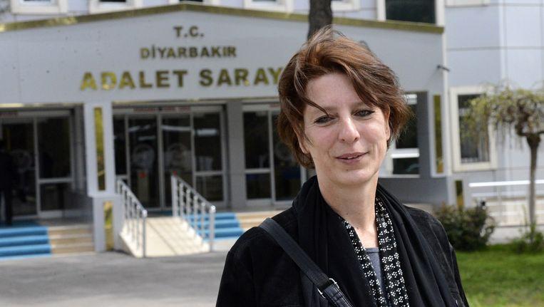 De Nederlandse journaliste Fréderike Geerdink poseert voor het gerechtsgebouw in het Turkse Diyarbakir. Beeld anp
