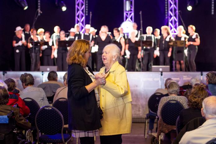 Sommige ouderen waagden zich vrijdagmiddag aan een dansje tijdens het meezingfestijn met levensliederenkoor Hart en Smart in de feesttent van Bruisend Nijverdal .
