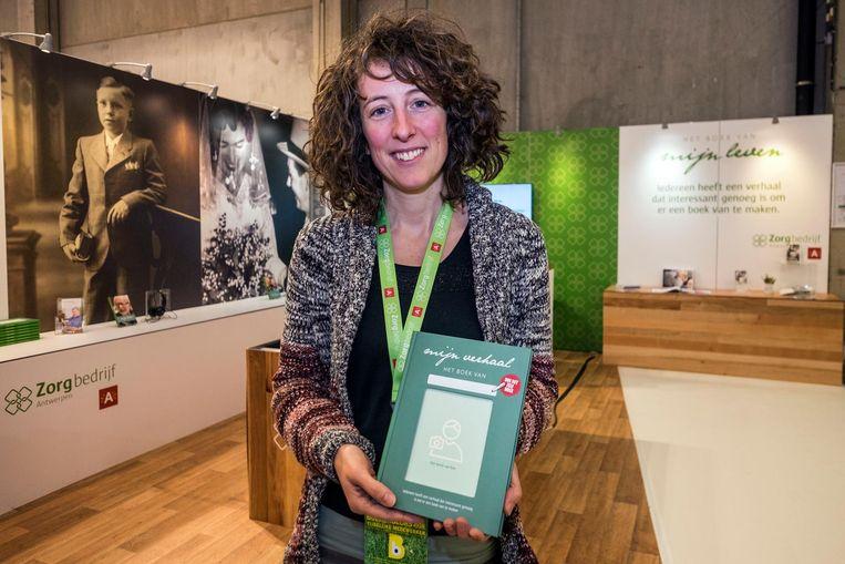 Sara Engels, levensverhaalschrijfster, toont het doe-het-zelfboek 'mijn verhaal'.