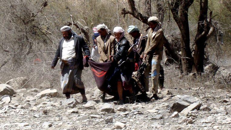 Leden van Al Qaeda dragen het lichaam van een strijdmakker die vandaag is omgekomen bij gevechten in Jemen. Beeld EPA