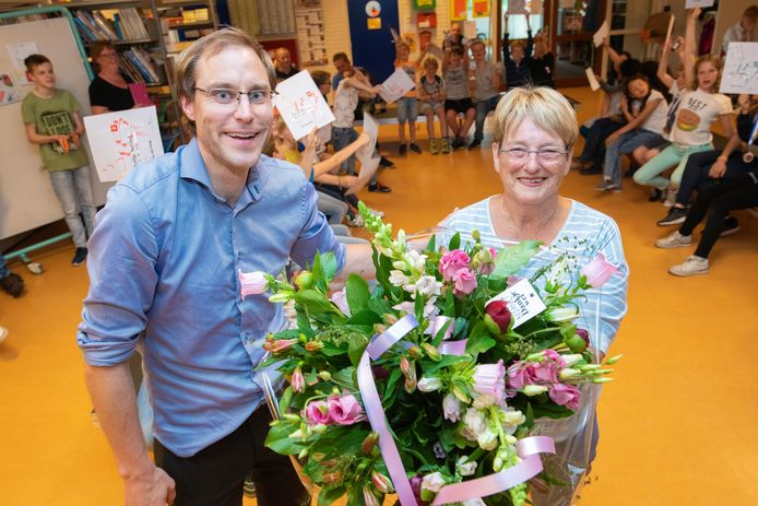 Carla van der Hulst neemt de bloemen in ontvangst van Martin van Bruggen, hij is de coördinator van Schaakclub de Schaakvrienden voor leerlingen van de Sjofar en de Horst.