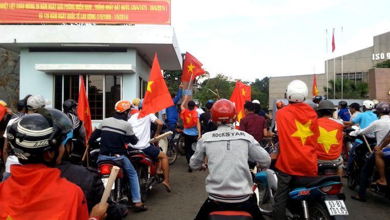 Betogers met Vietnamese vlaggen bij een fabriek in het zuiden van het land tijdens een ant-China-protest. Beeld reuters