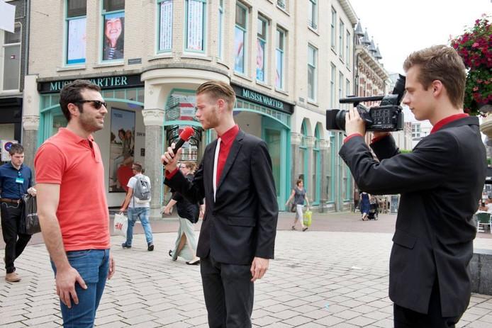 Benjamin Beernink (met microfoon) en Mitchel Bongers van En Nou Wij FF aan het werk in de straten van Arnhem. foto Marc Pluim