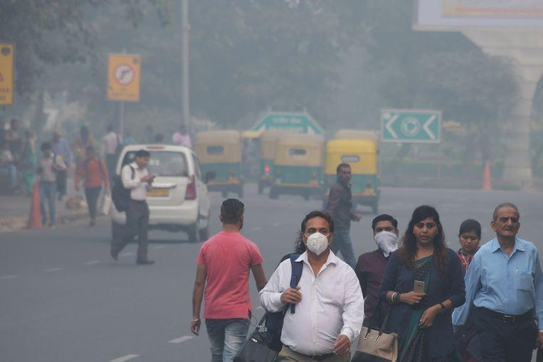 Mensen lopen over straat in Delhi.  Beeld AFP