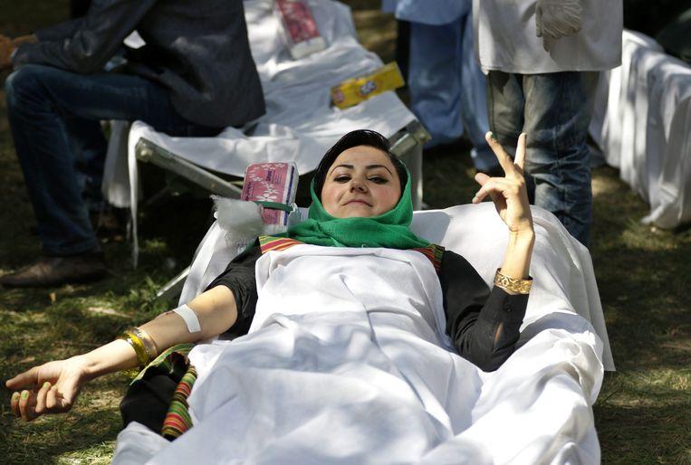 Een Afghaanse vrouw doneert bloed voor militairen die gewond zijn geraakt bij de gevechten in Kunduz. Beeld epa