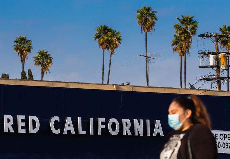 Een Amerikaanse vrouw loopt op straat met een mondkapje. Beeld AFP