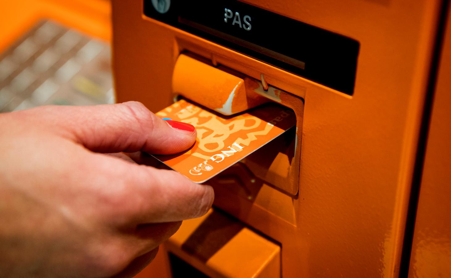 Een klant gebruikt een pinautomaat van de ING bank.