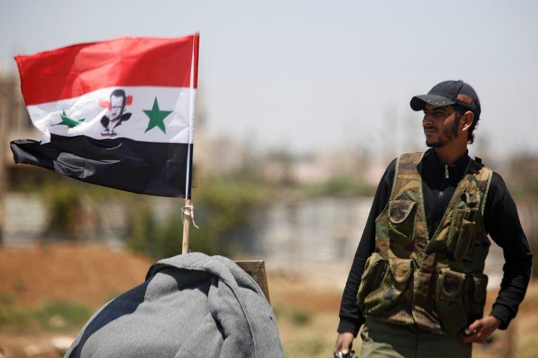 Een soldaat van het Syrische leger staat naast een Syrische vlag.