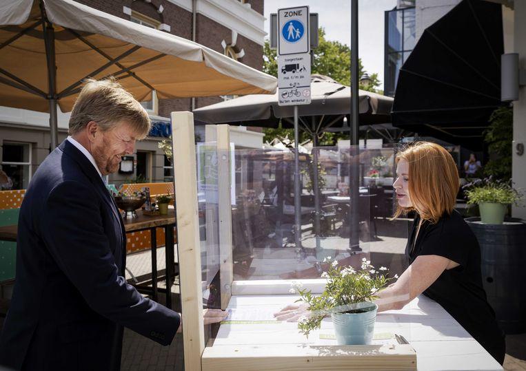 Koning Willem-Alexander praat in juni dit jaar met een horeca ondernemer bij een intake van een terras tijdens een bezoek aan de gemeente Apeldoorn. Beeld ANP