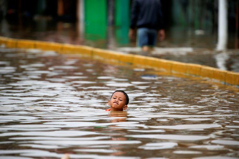 Een jongen kan nog net het hoofd boven water houden als hij zwemmend probeert zich te redden in het oprukkende water in het district Jatinegara in Oost-Jakarta. Beeld REUTERS