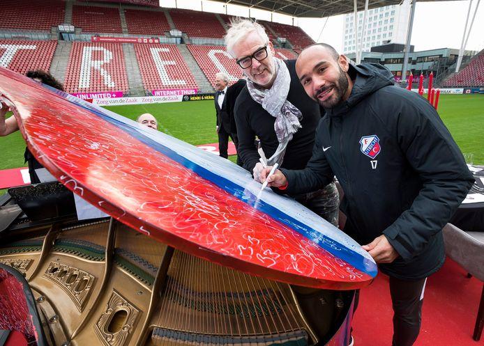 Sean Klaiber signeert de beschilderde vleugel die geveild wordt voor het goede doel. Links de kunstenaar die de vleugel beschilderde.