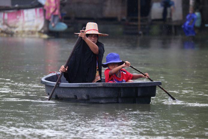 Een vrouw en kindje na hevige overstromingen in Thailand.