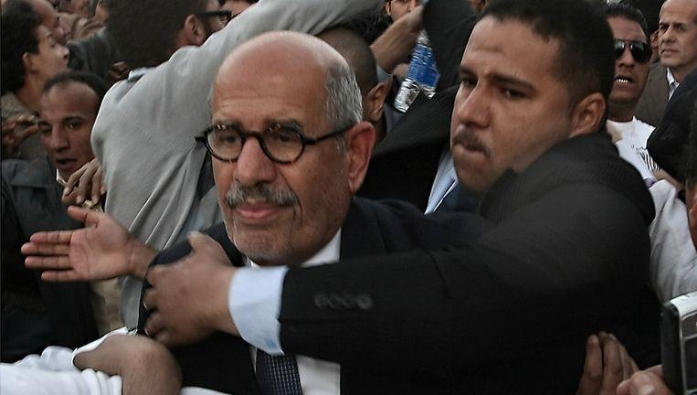 Mohamed ElBaradei baant zich - met hulp - een weg door de menigte. (boven en onder) Beeld afp