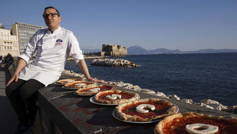 Italiaanse pizzabakker Gino Sorbillo heeft de letters U N E S C O met kaas op zijn pizza's gelegd. Beeld afp