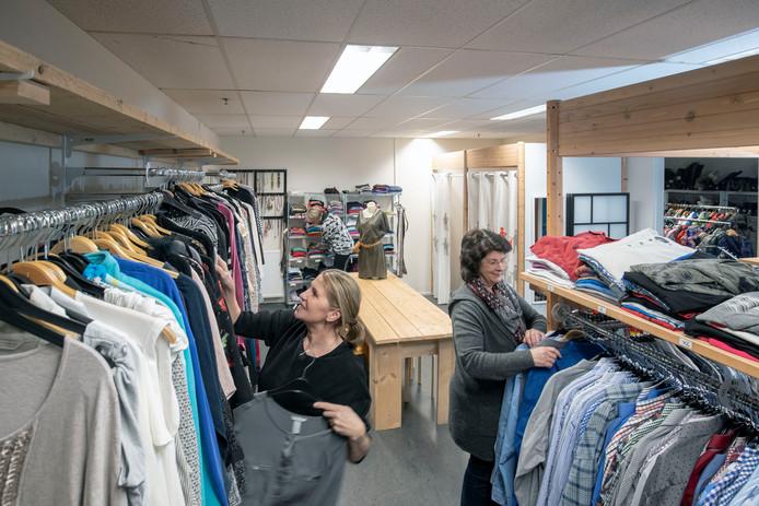 Vrijwilligers op de nieuwe locatie van de kledingbank.