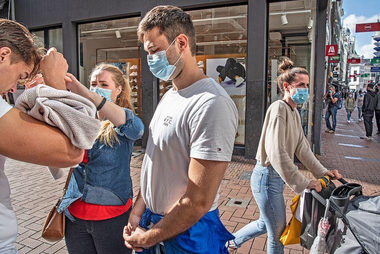 Bij de ingang van de Kalverstraat zetten veel  bezoekers braaf een mondkapje op. Even later hangt het in veel gevallen weer op de kin. Beeld Guus Dubbelman / de Volkskrant