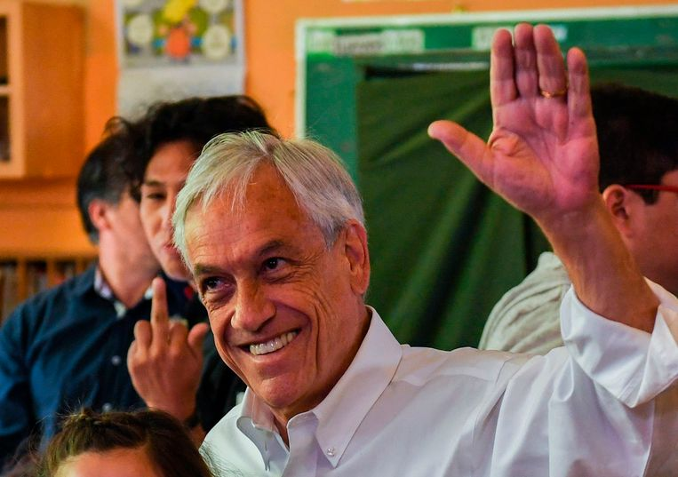 Sebastián Piñera is niet bij iedereen geliefd, zoals de middelvinger op de achtergrond weergeeft.