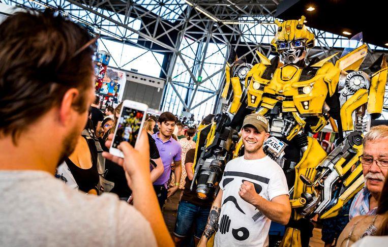 Een bezoeker gaat op de foto met een transformer. Beeld anp
