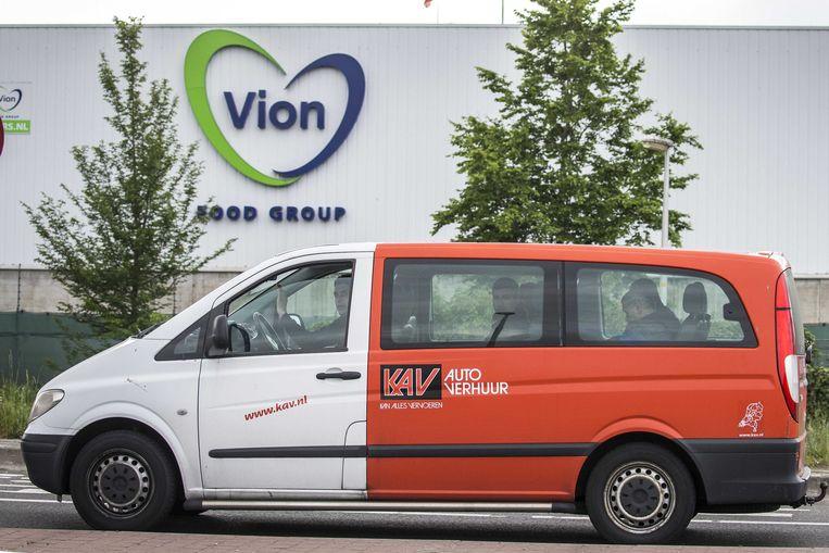 Arbeidsmigranten verlaten in een busje het slachthuis van Vion in Groenlo. Beeld ANP