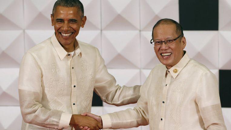 Obama, in een traditioneel Filipijns baronghemd, schudt de hand van de Filipijnse president Benigno Aquino op het galadiner van de Asia-Pacific Economic Cooperation.