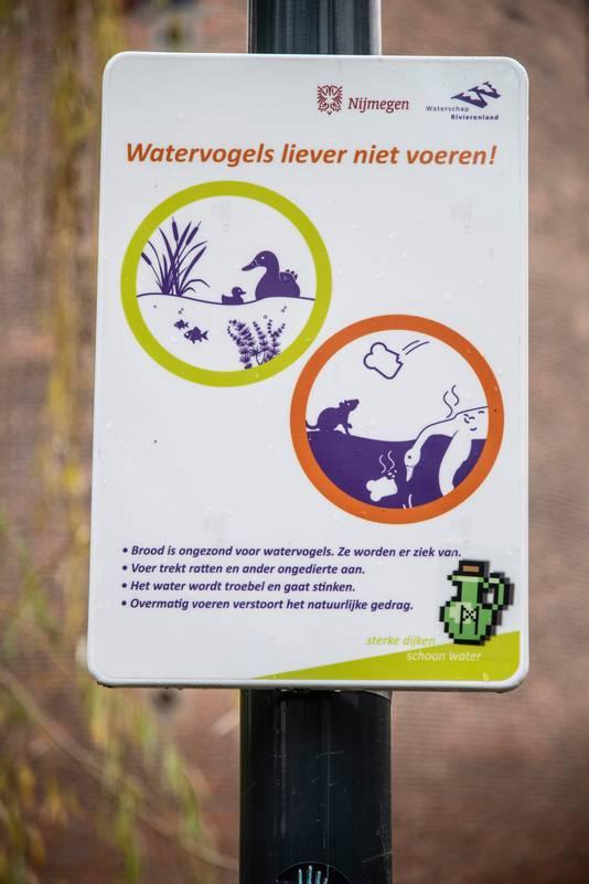 Aan een lantaarnpaal bij de vijver in Kronenburgpark hangt een bord met de tekst: Watervogels liever niet voeren!