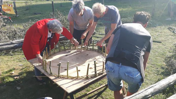 Bewoners in Orthen vlechten riet voor de maquette van de uitkijkpost.