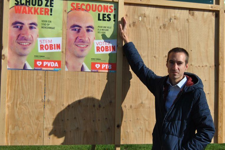 Een misnoegde Robin Tonniau bij de affiches van PVDA*PTB.