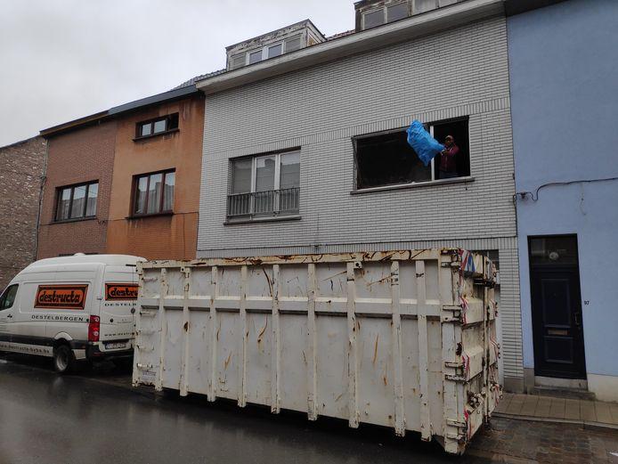 De werkmannen gooien vuilniszak na vuilniszak in de container.