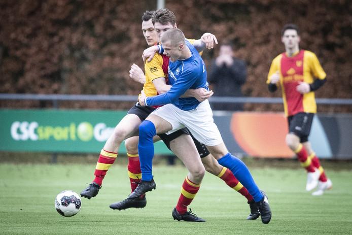Jesper Middelkamp van de Zweef wordt vastgehouden door een speler van Stevo.