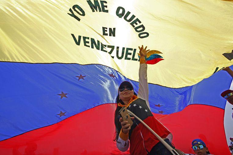 Een vrouw houdt een Venezuelaanse vlag vast tijdens het 'Venezuela Aid Live'-concert op de Tienditasbrug in Cúcuta, Colombia. Beeld AFP