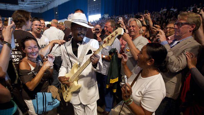 De Amerikaanse bassist Larry Graham loopt door het publiek naar het podium.