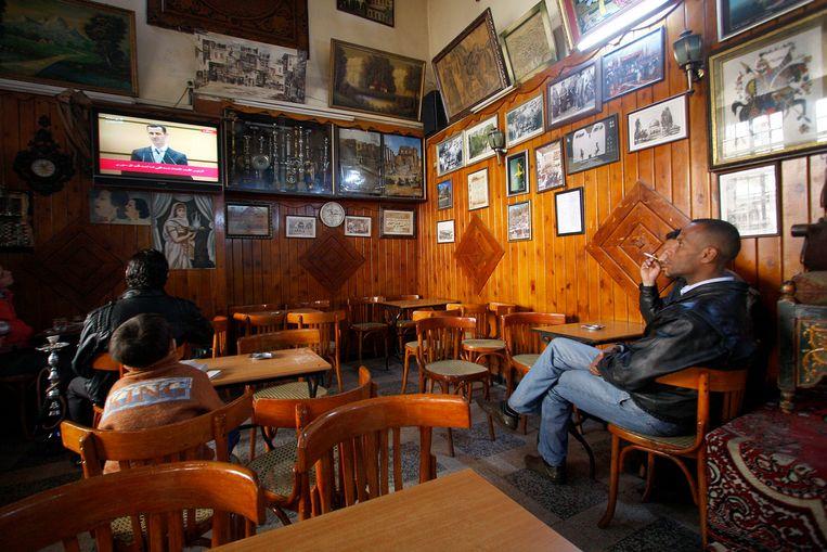 Syriërs kijken naar de toespraak; thuis of in het café. Beeld AP
