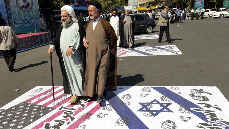 Iraanse mannen lopen over een poster met een Amerikaanse en Israëlische vlag, tijdens een protest in Teheran, afgelopen zaterdag. Beeld EPA