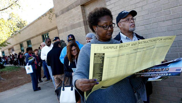 Mavis Wilson bekijkt in Charlotte het stembiljet voor vroegstemmers op 24 oktober 2016. 'Het parlement van North Carolina was de auteur van een 'monsterwet', die het zwarte kiezers lastig maakte te gaan stemmen.' Beeld afp