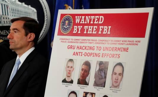 John Demers van het Amerikaanse ministerie van Justitie naast een poster met de zeven Russische inlichtingenofficieren tijdens de persconferentie.