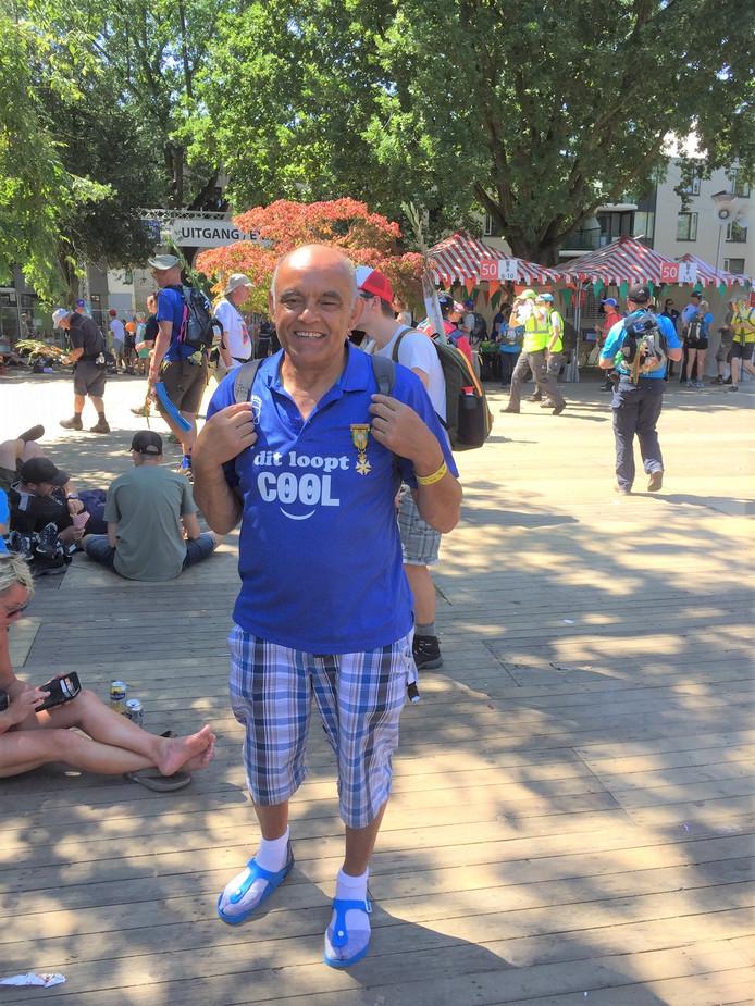 """Albert Eckhardt (71), tijdens de vierdaagse van vorig jaar. Aan zijn voeten de blauwe slippers. Hij raadt het iedereen aan. ,,Niks geen problemen met blaren."""""""