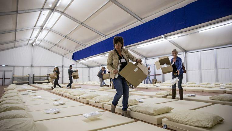 Medewerkers van Centraal Orgaan opvang asielzoekers (COA) richten een noodpaviljoen in voor de opvang van asielzoekers. Beeld anp