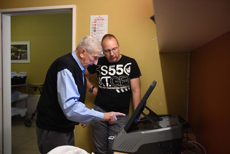 Bewoner Maurice Valkenaers (94) leert werken met de stemcomputer.
