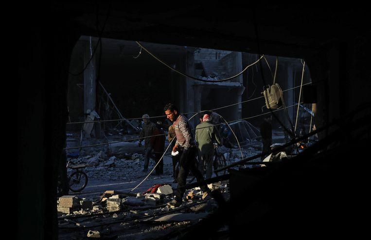 Bewoners doorzoeken het puin na de luchtaanval van zaterdag.