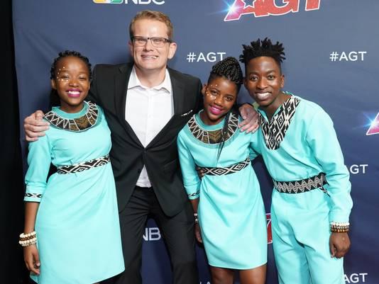Dirigent Ralf Schmitt poseert samen met drie leden van het Ndlovu Youth Choir vlak voor de halve finale van America's Got Talent.