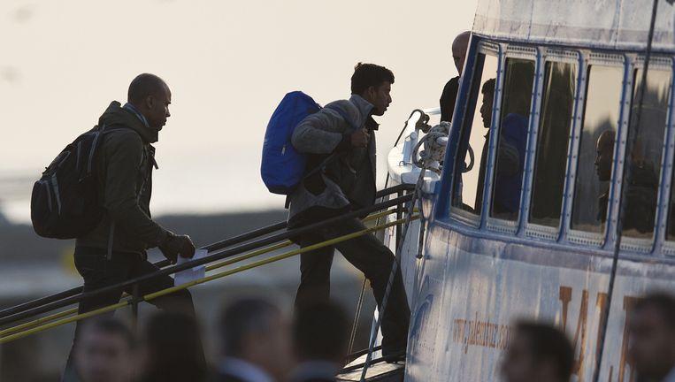 Migranten worden in de haven van Mytilini op Lesbos teruggestuurd naar Turkije. Beeld ap