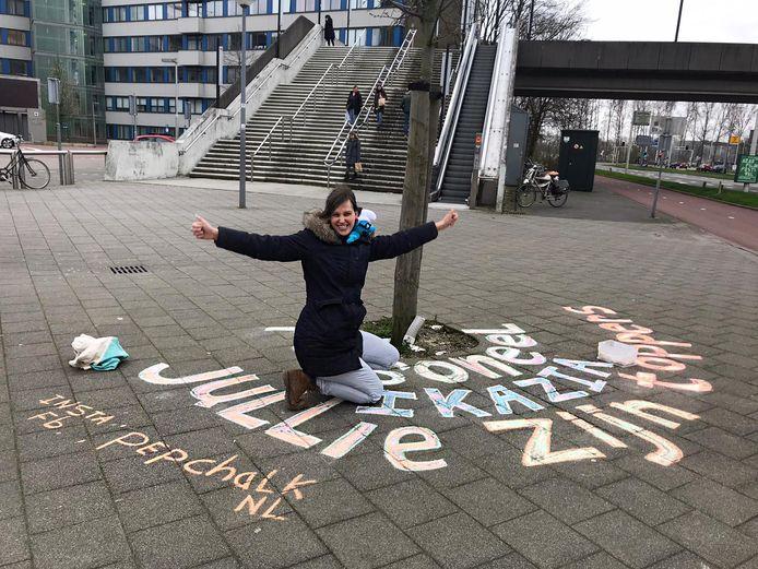 Eva van Woerkom bezig met haar 'pepchalk' bij het Ikazia Ziekenhuis in Rotterdam. Ze wil er de vele zorgmedewerkers die zich onder meer vanwege het coronavirus de benen onder hun kont uit rennen, een welgemeende opsteker mee geven.