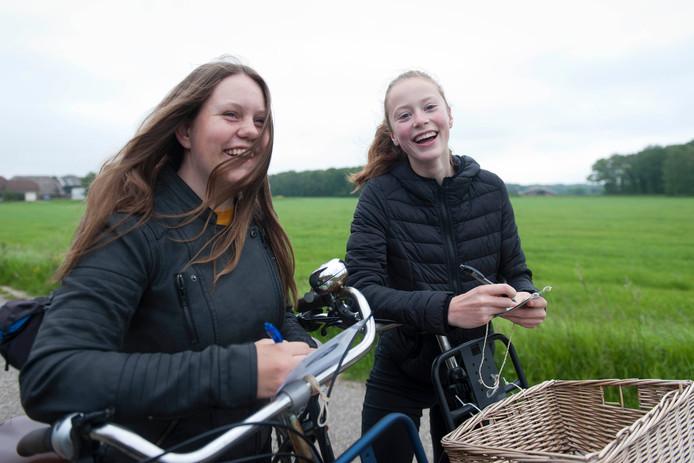 Iris (l) en Yara kruisen tijdens de fietsbingodauwtraptocht in Olst een nummer aan op hun bingokaart. En verder moeten ze op de 25 kilometer lange route.
